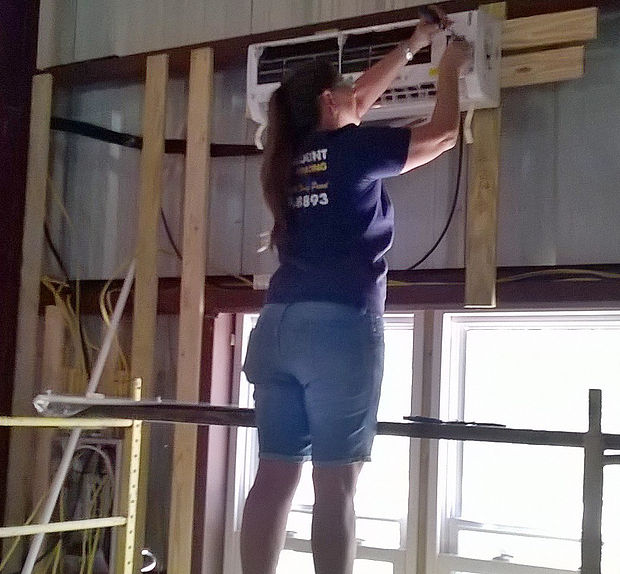 woman with a screw driver serving an air conditioner
