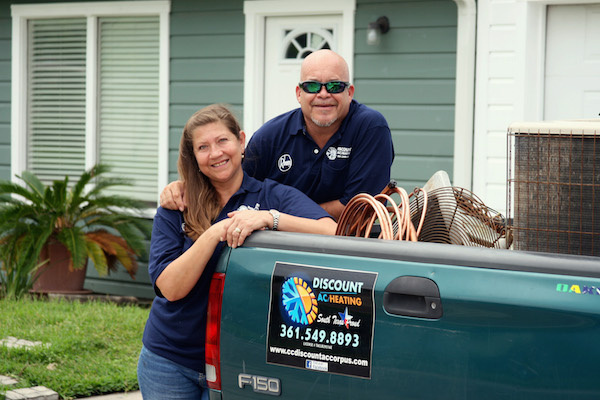 leonard and judy reyes discount air conditioning and heating stand next to a green work truck smiling